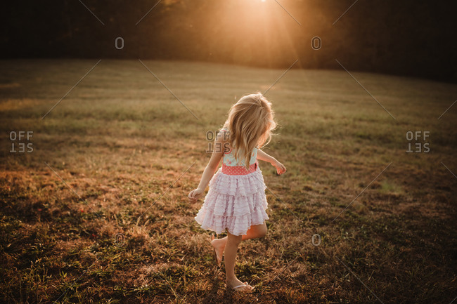 Blonde girl dancing in a field at sunset