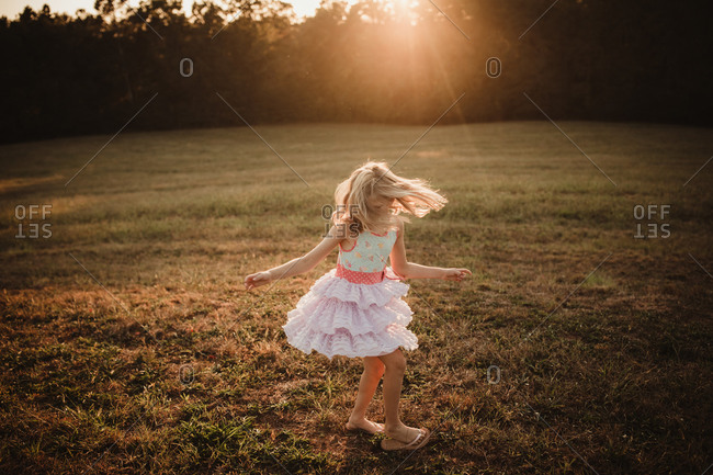 Blonde girl twirling in a field at sunset