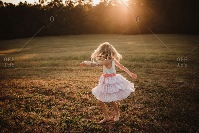 Blonde girl dancing outdoors at sunset