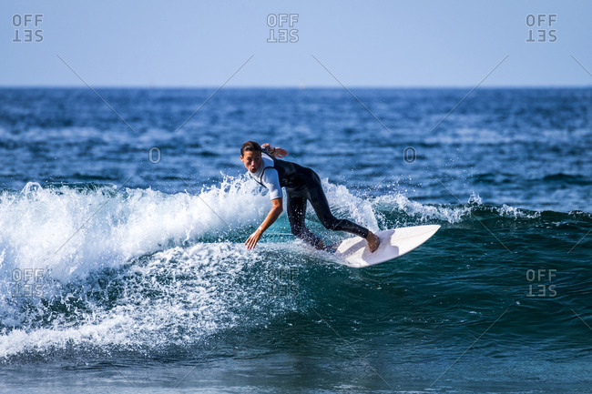 Tenerife, Spain, young active boy surfing in the blue ocean water