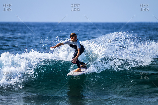 Tenerife, Spain, a young active boy surfing in the blue ocean water