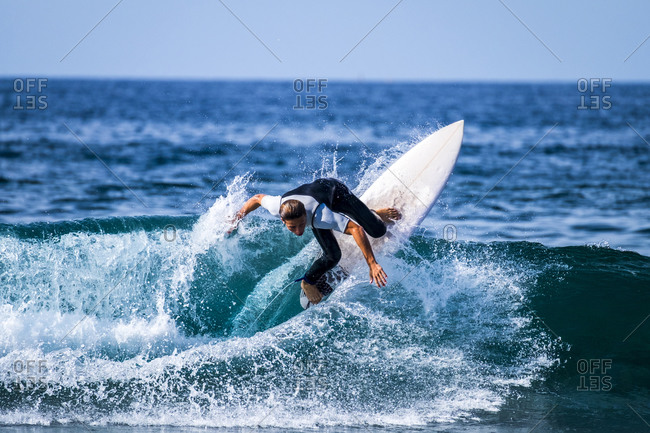 Young active boy surfing in the blue ocean water in Tenerife, Spain