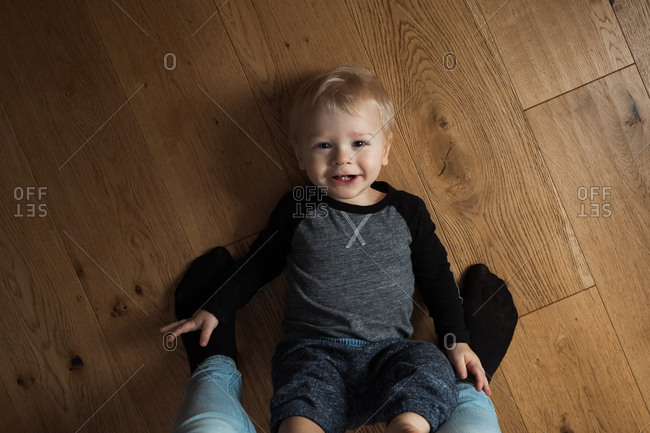 Baby boy lying between mom's feet on floor looking up smiling