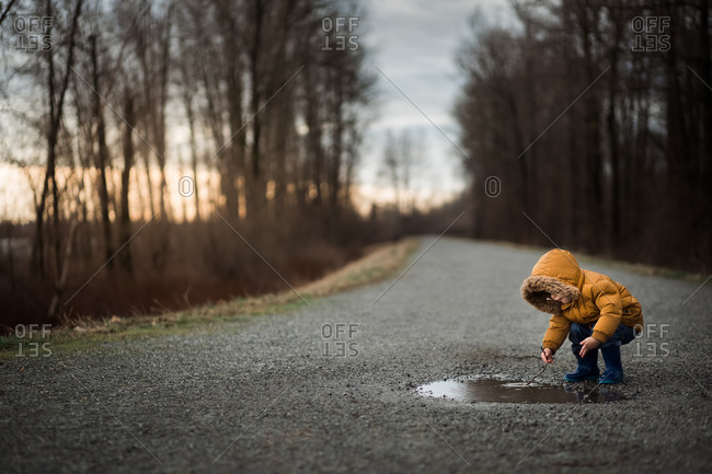 Toddler boy playing in a puddle with a stick on a rural path