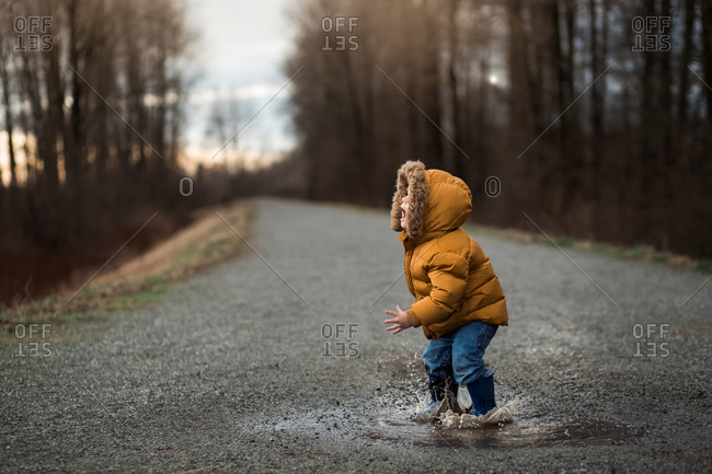 Toddler boy jumping in a puddle with a stick on a rural path