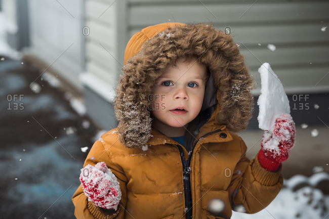 Toddler boy wearing yellow puffer jacket holding a snowy chunk of ice
