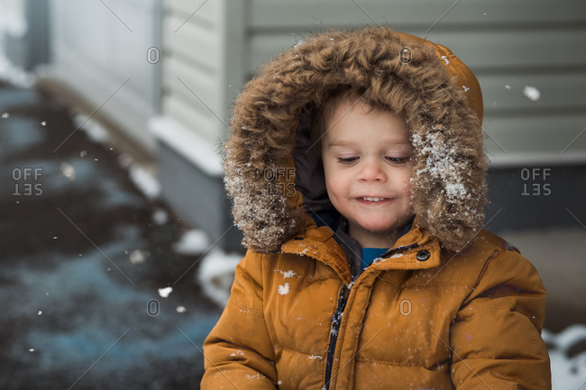 Happy toddler boy wearing yellow puffer jacket outside in the snow