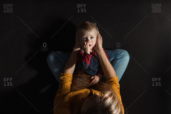 Overhead view of a sad baby in his mother's lap