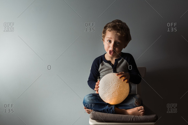 Young boy sticking tongue out while holding round moon lamp