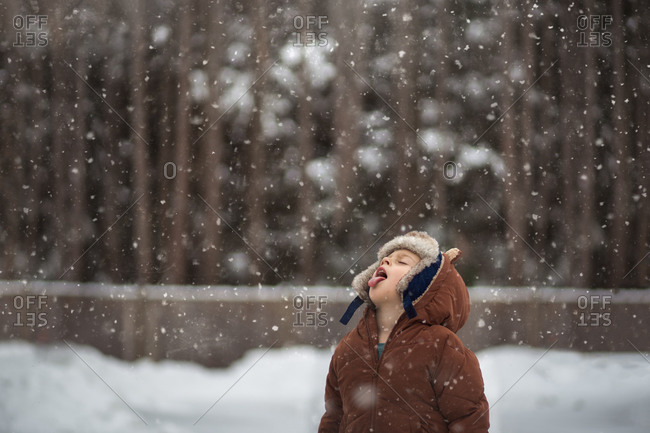 Little boy catching snowflakes on his tongue