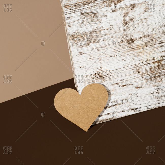 Cardboard heart on a wooden surface against two shades of brown