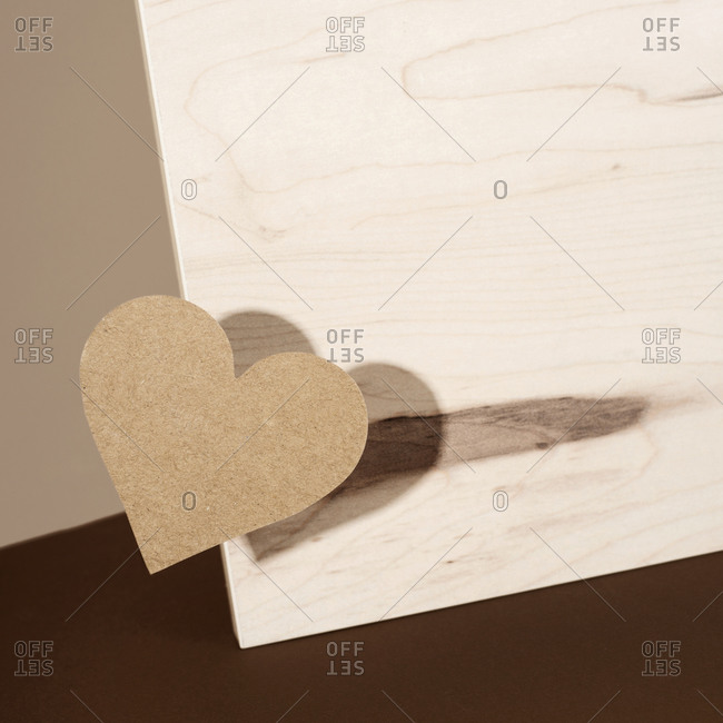 Cardboard heart on a wooden surface against brown background