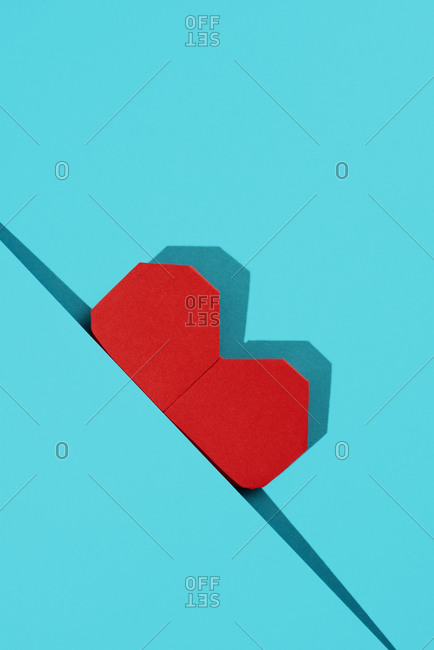 Red origami heart on a blue paper background