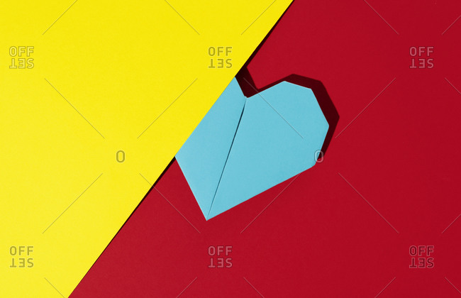Blue origami heart on a red and yellow paper background
