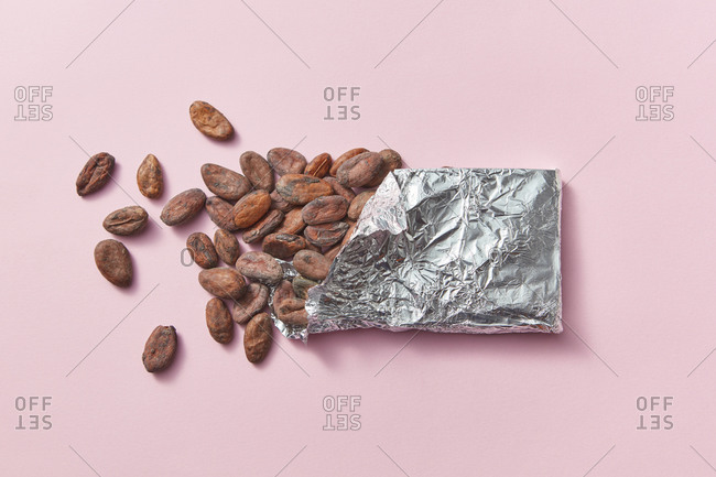 Chocolate bar made up of natural organic cocoa beans in tin foil on a light pink background with copy space.