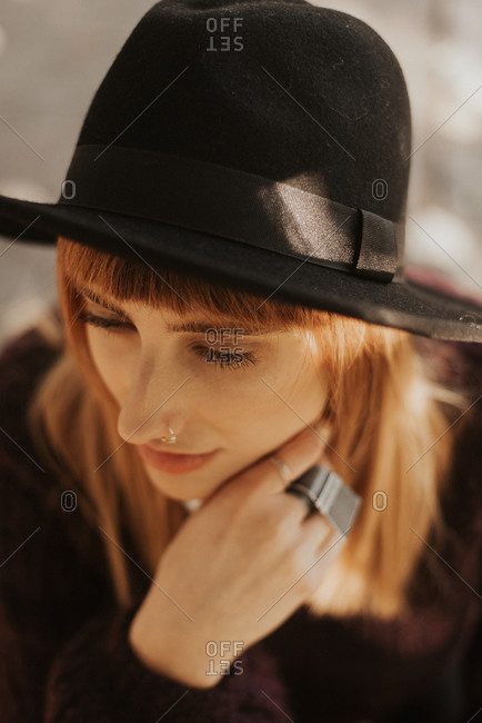 Stylish young woman wearing black hat looking away