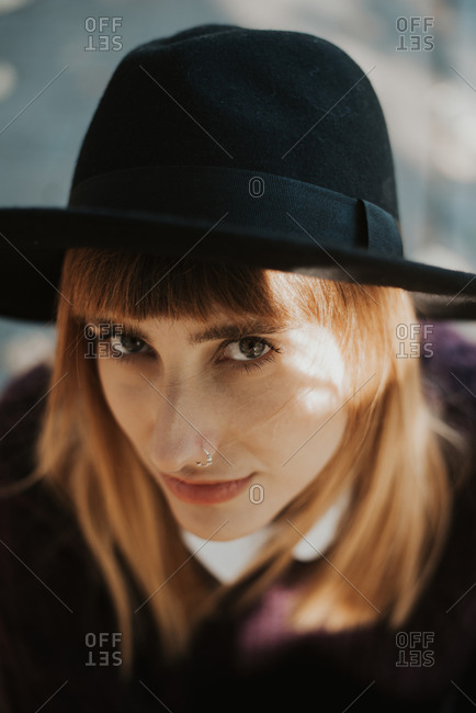Close up of a stylish young woman wearing black hat
