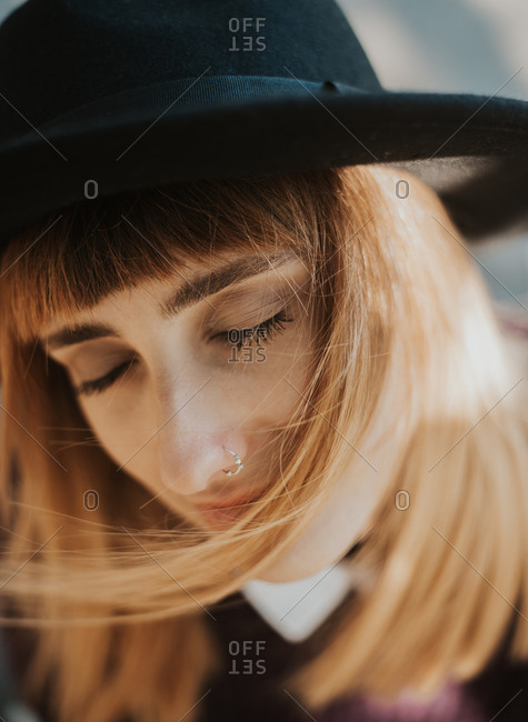 Wind blowing stylish young woman's hair as she closes her eyes