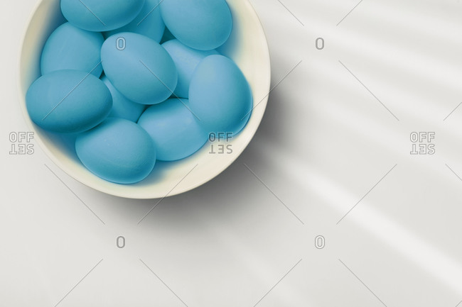 Painted easter eggs in a white bowl on a table