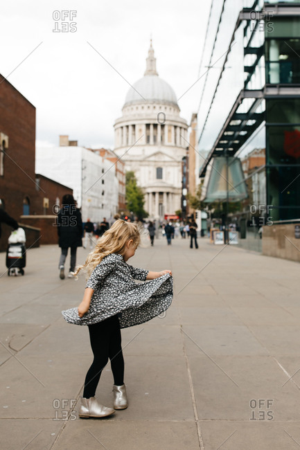 Little girl dancing in the street in front of St Paul's Cathedral in London