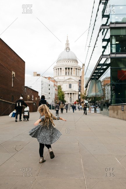 Young girl dancing in the street in front of St Paul's Cathedral in London