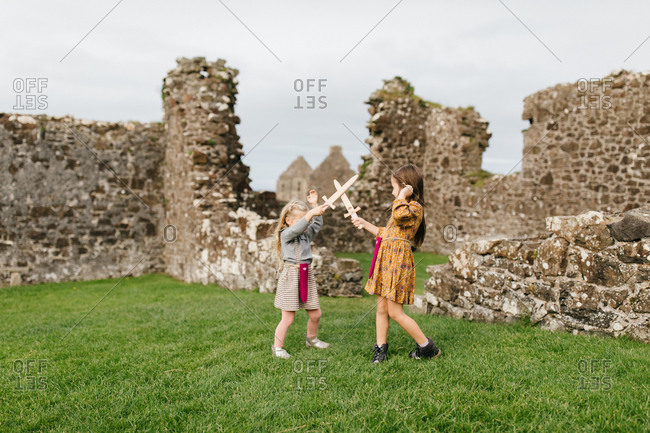 Two girls play sword fighting by the remains of the Dunluce Castle in Northern Ireland