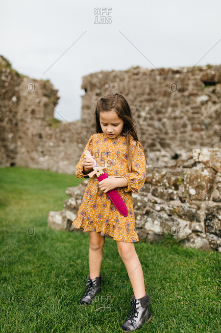 Young girl holding toy sword by the remains of the Dunluce Castle in Northern Ireland