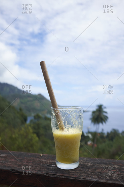 Fruity cocktail on railing overlooking the coast of Mo'orea