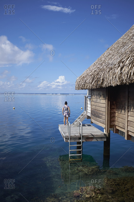 Woman looking out from dock attached to a thatched roof bungalow on the coast of Mo'orea