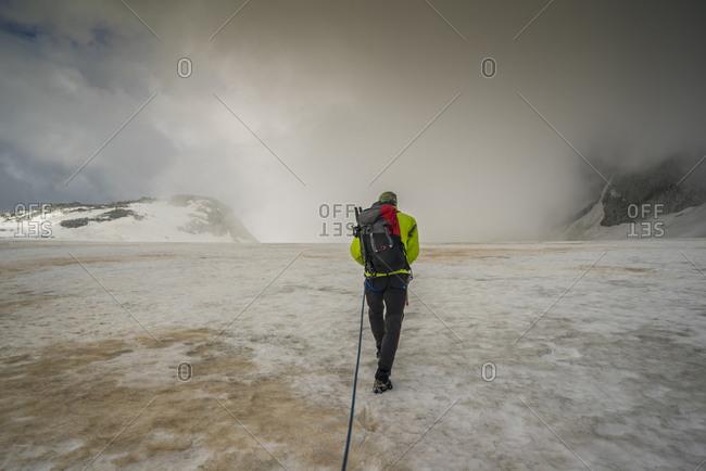 Italy, Trentino Alto Adige, Valdaone - July 4, 2016: Climber crossing Vedretta di Fumo Glacier from Lobbia Altato Passo Val di Fumo