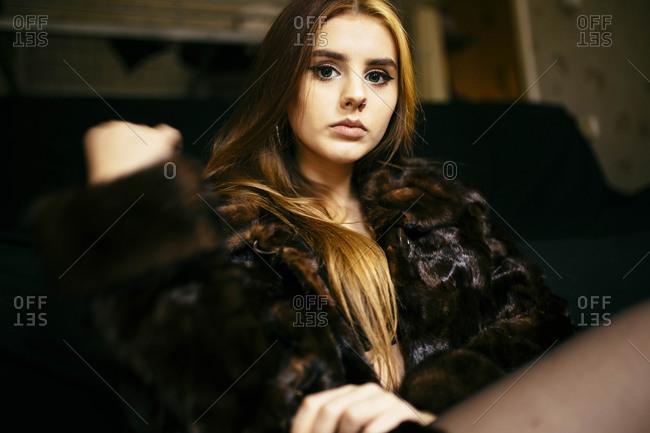 Woman in a fur coat sitting