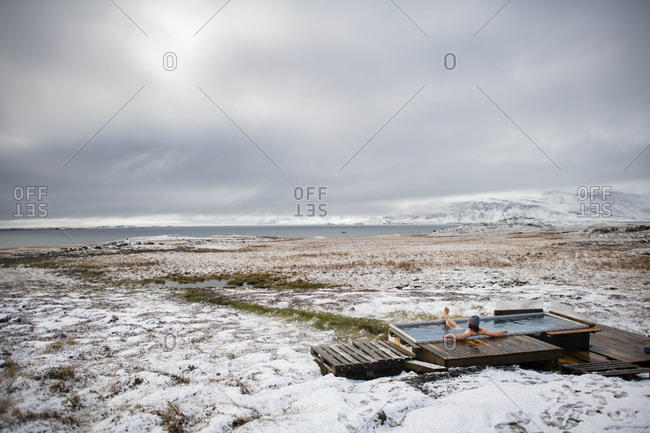 A man enjoying a natural hot springs after a fresh snow, Iceland.