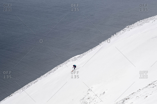 A woman backcountry skiing to the ocean in Iceland.