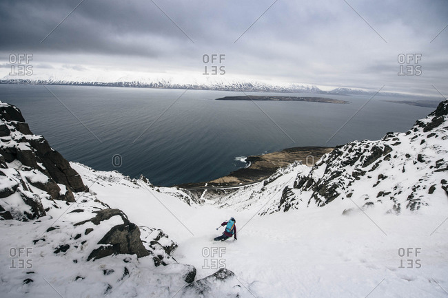 A woman backcountry skiing to the ocean at in Iceland.