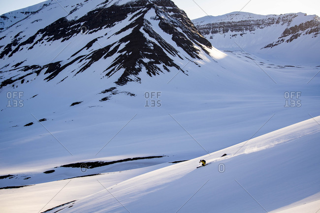 A man backcountry skiing at sunset in Iceland.