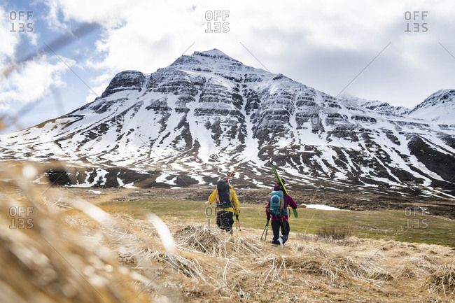 Two backcountry skiers hiking to the snow in Iceland.