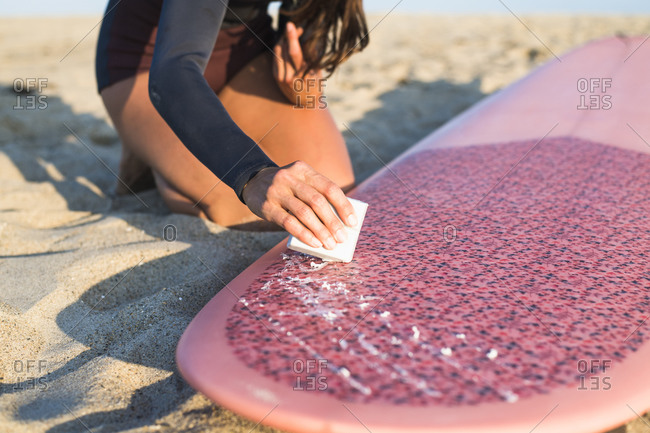 Water woman waxing her new surfboard in preparation for sunset surf