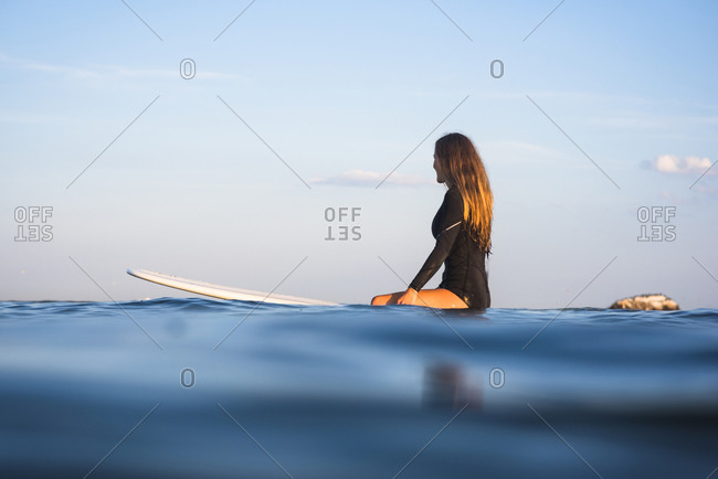 Water women friends surfing together at sunset