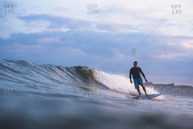 Rhode Island, Narragansett - July 12, 2019: Middleaged man surfing at sunset