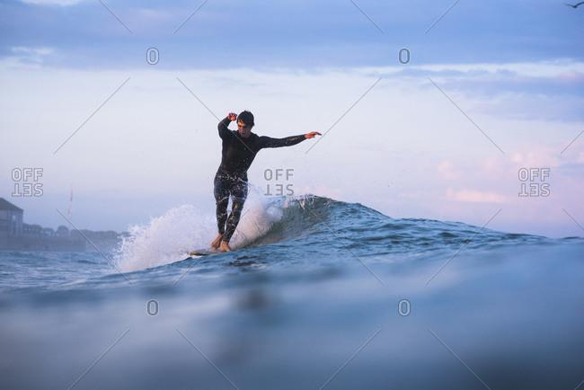 Rhode Island, Narragansett - July 12, 2019: Young man surfing at sunset
