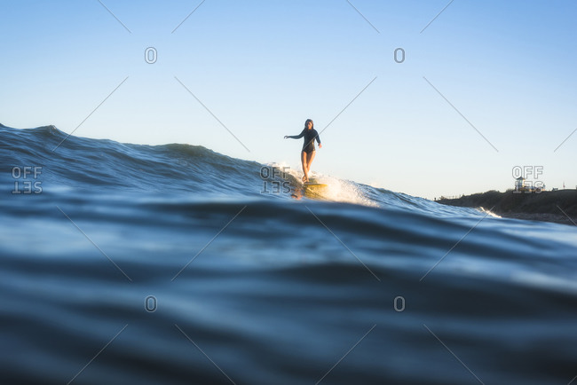 Woman surfing at sunset