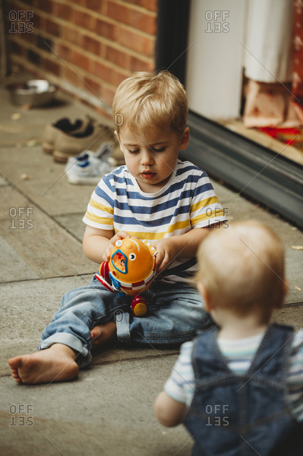 Toddler sitting outside playing with toy, watched by baby brother