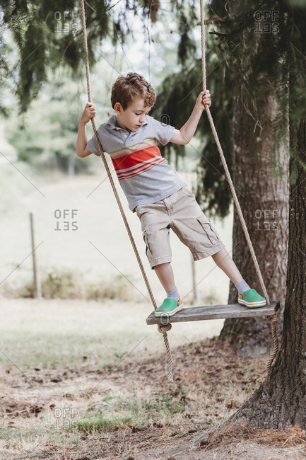Front view of boy standing on swing, swinging side-to-side under trees