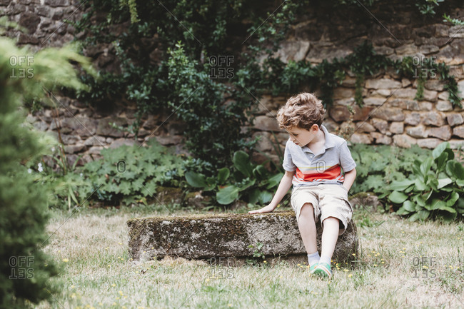 Front view of boy sitting on moss-covered rock-bench