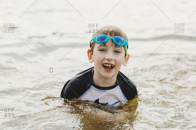 Boy wearing goggles coming out of the water