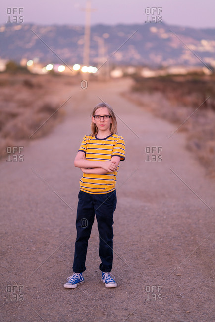 Tween standing on dirt road looking at camera at twilight