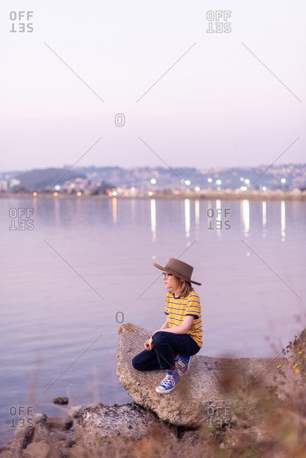 Tween with wide brimmed hat looks out over bay at twilight