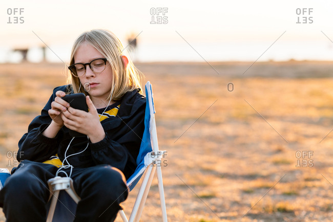 Tween sitting in camp chair looking at phone with earbuds