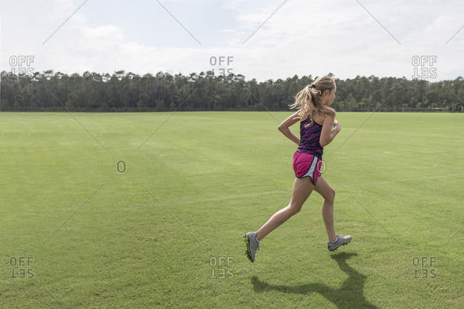 Teen girl cross country runner practicing sprints at soccer field