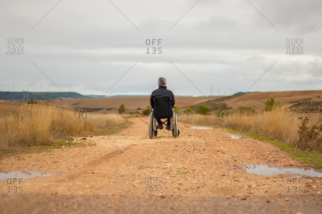 Rear vision of a disabled man in a wheelchair alone in a path